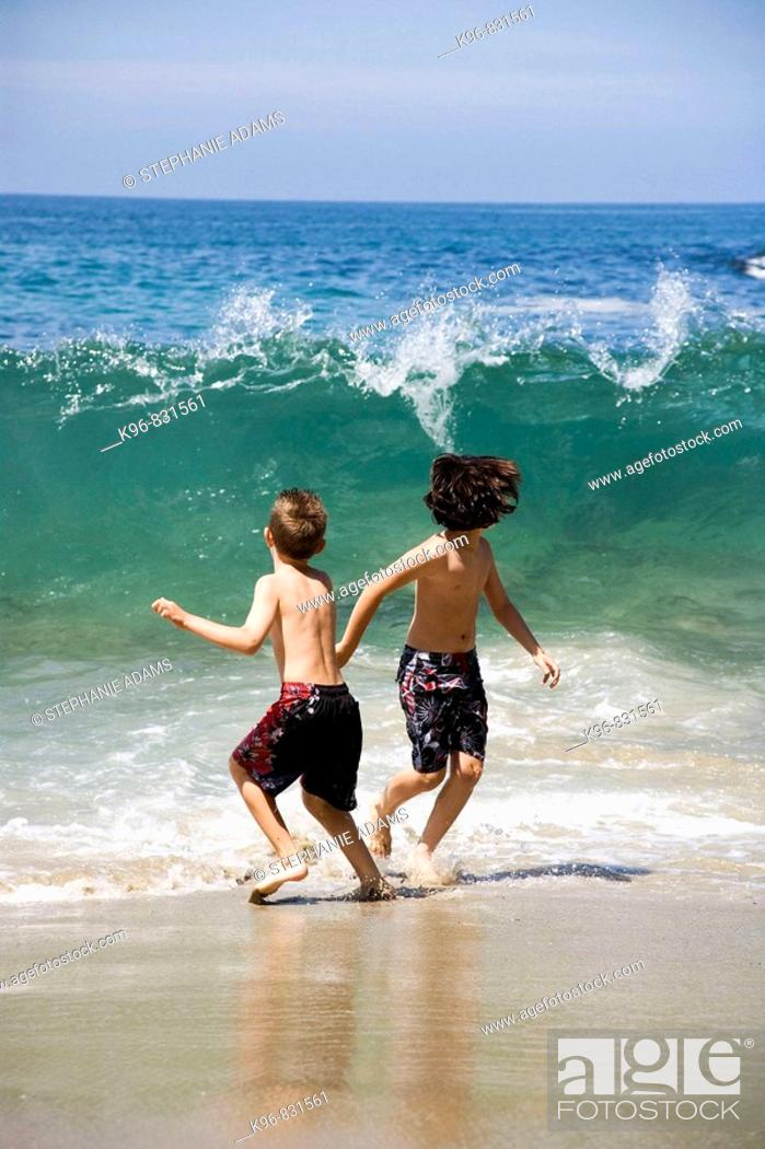 Stock Photo: two boys running from a wave.