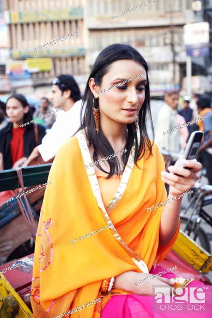 Stock Photo: Young woman sitting in a rickshaw and using a mobile phone.