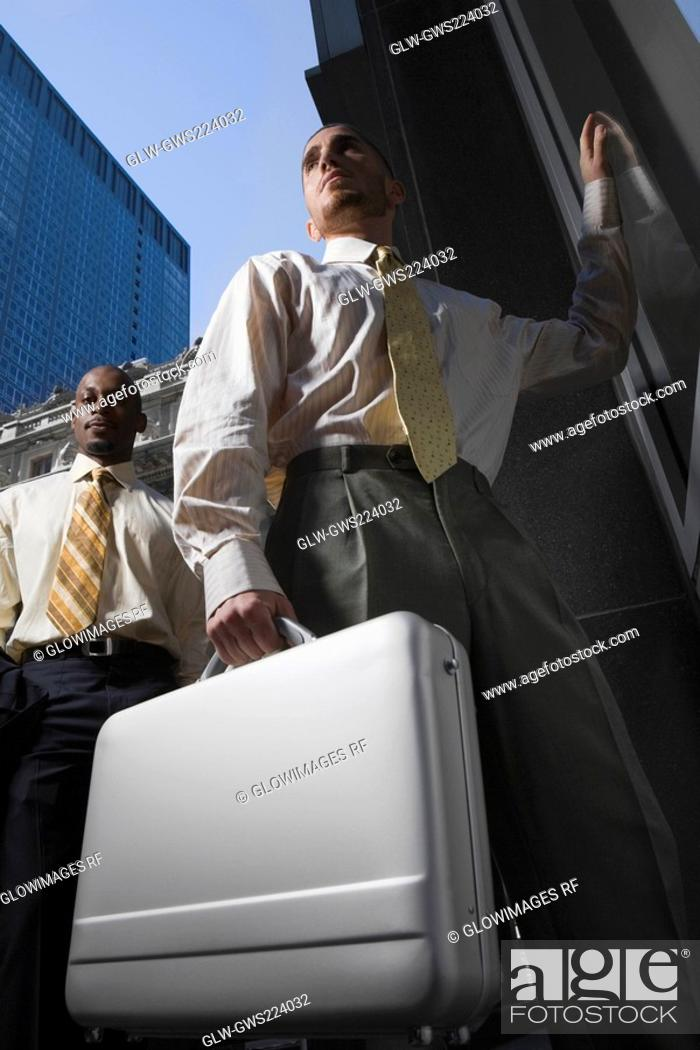 Stock Photo: Low angle view of a businessman holding a briefcase and another businessman standing behind him.