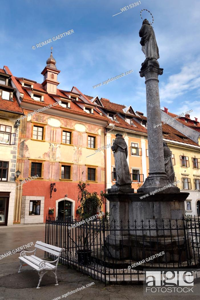 Stock Photo: Pink frescoes on Old Town Hall building in the Town Square of Skofja Loka Slovenia with Mark of Mary ionic column monument.