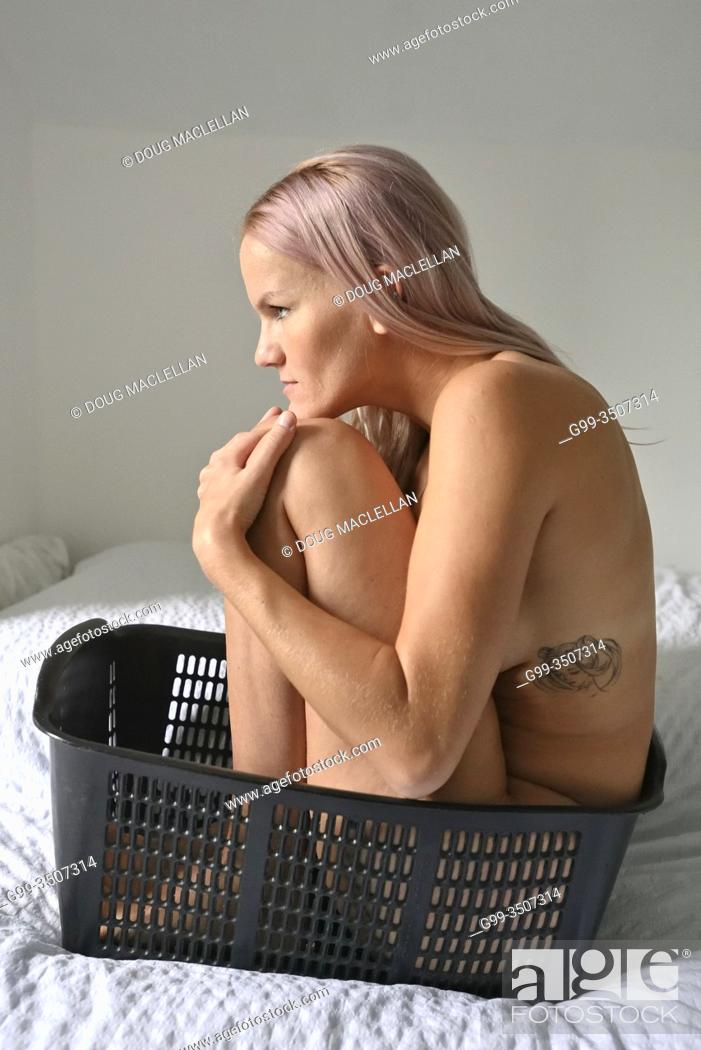 Photo de stock: A naked woman sits in a plastic basket on the bed in the autumn in Canada.