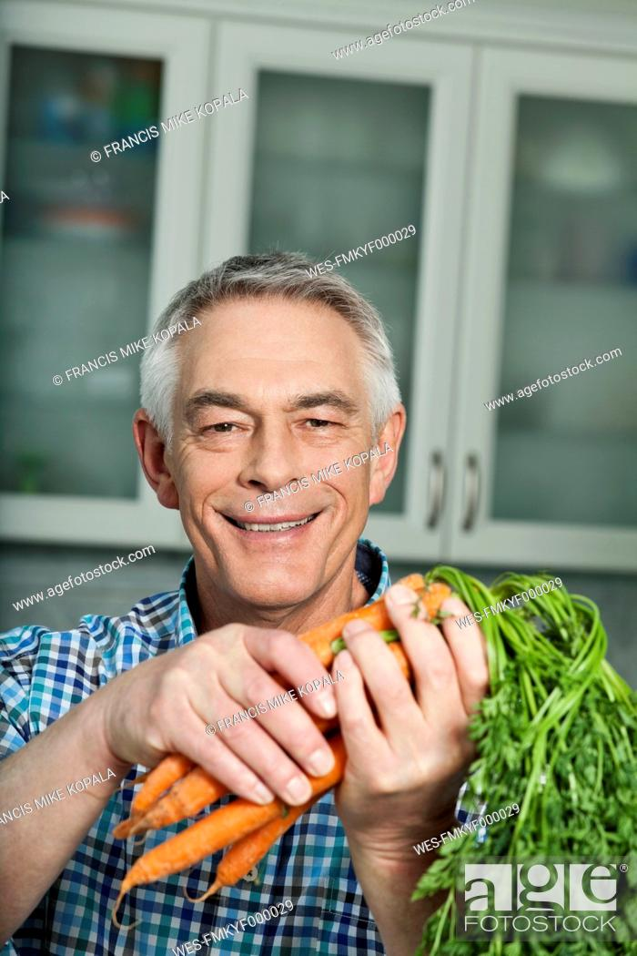 Stock Photo: Germany, Berlin, Senior man holding carrots, portrait.