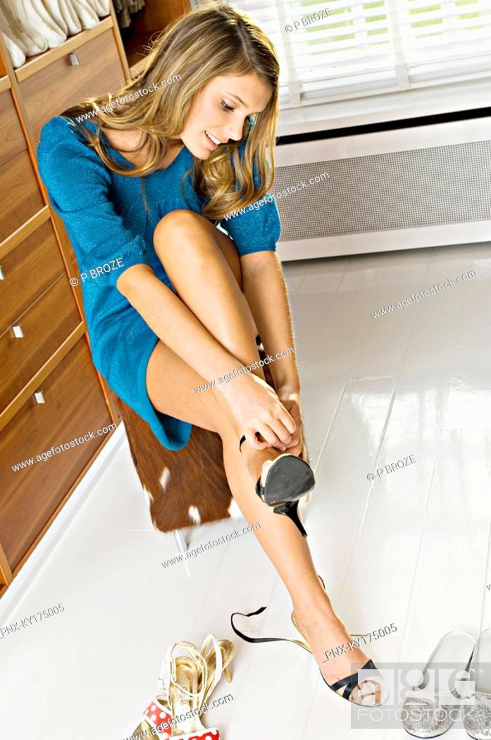Stock Photo: Young woman putting on high heels and smiling.