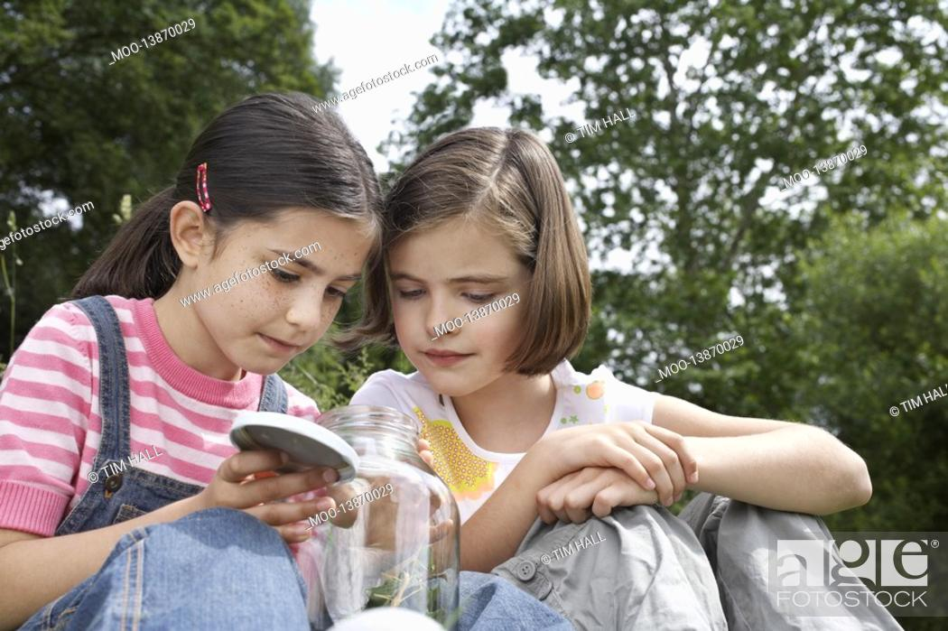 Stock Photo: Two girls 7-9 examining jar of insects outdoors.