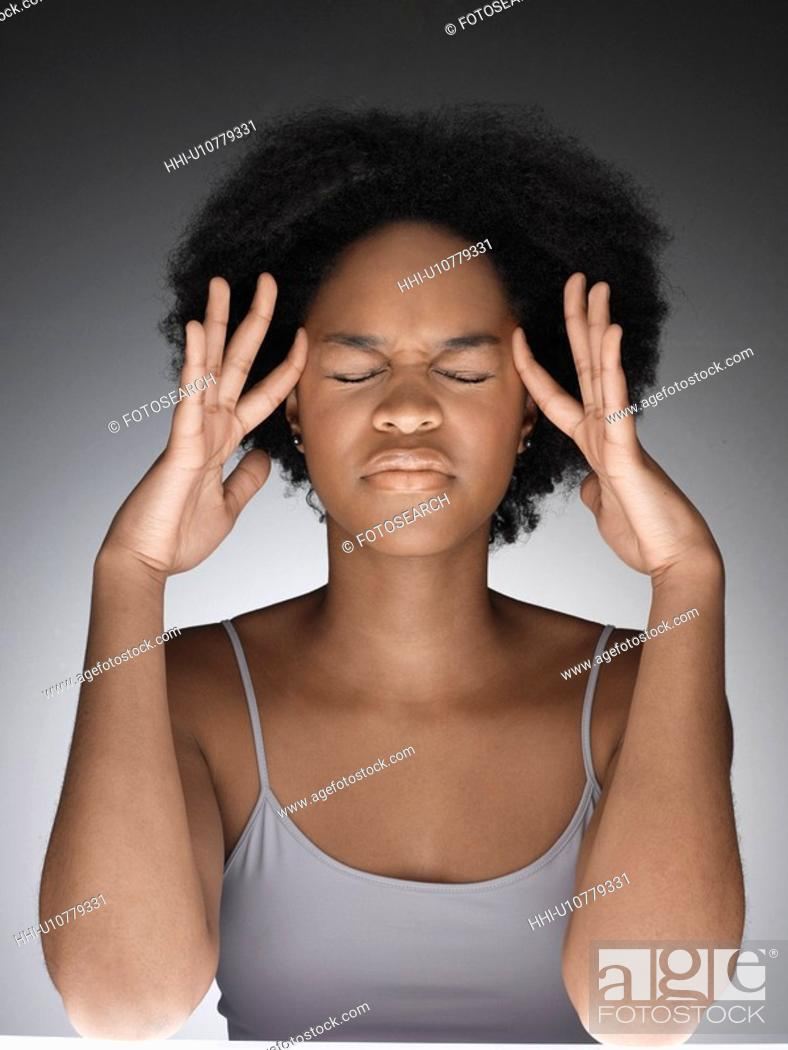 Stock Photo: Young woman thinking with hands on face.