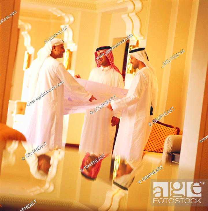 Stock Photo: Arab businesspeople discussing architectural sketch.