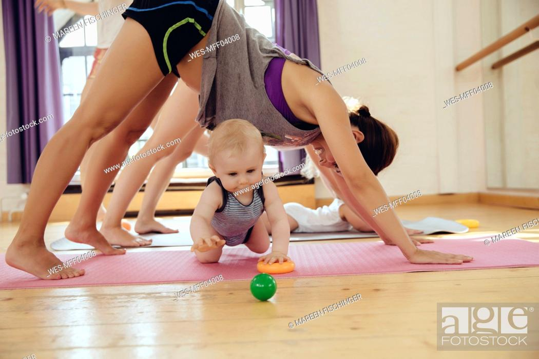 Stock Photo: Two mothers working out on yoga mats with babies playing around them.