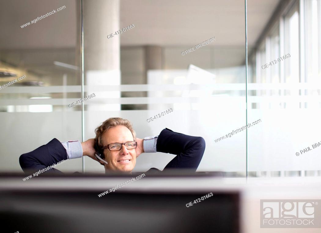 Stock Photo: Businessman talking on headset in office.