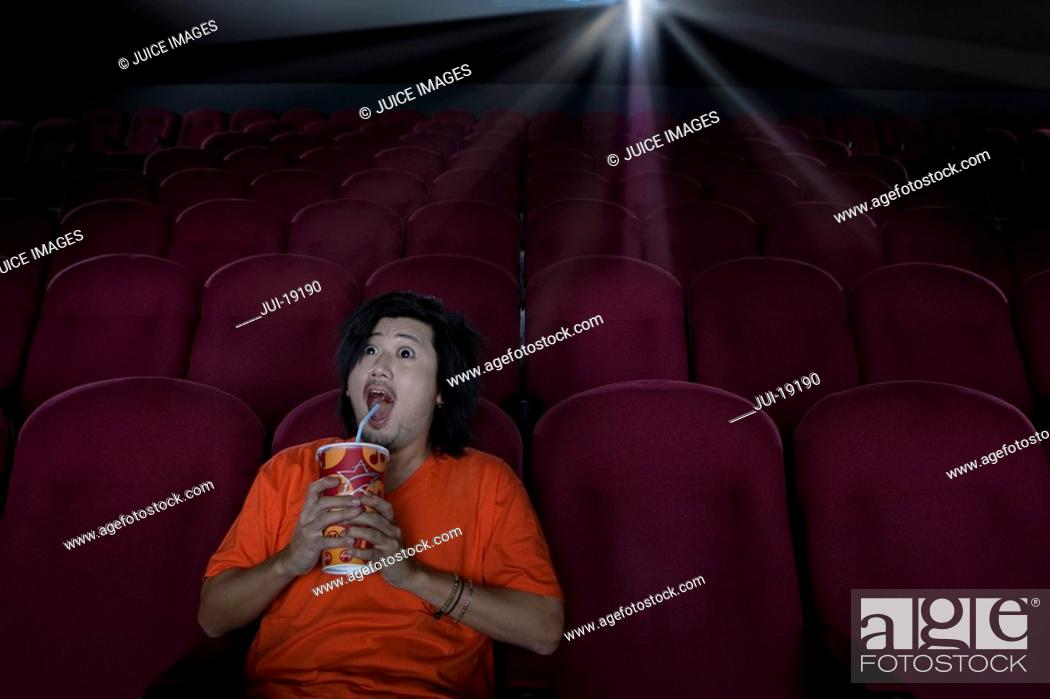 Stock Photo: Man with drink in empty cinema making face.