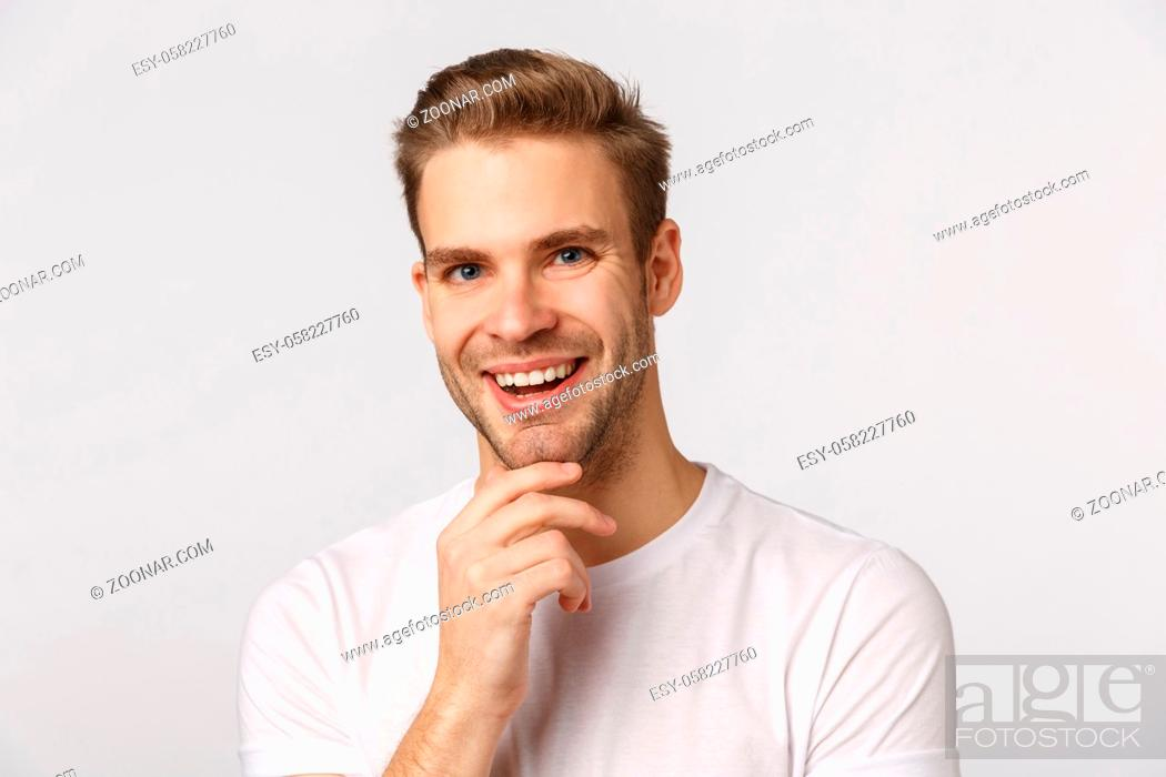 Stock Photo: Very good. Intrigued and pleased thoughtful young man, smiling satisfied nod in agreement, touching chin, agree with friend, made-up good plan, give approval.
