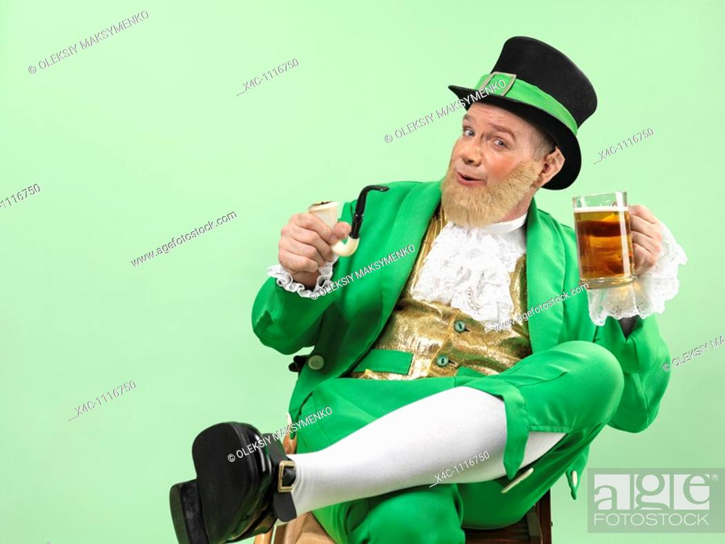Stock Photo: Cheerful Leprechaun in bright green clothes holding a smoking pipe and a beer.