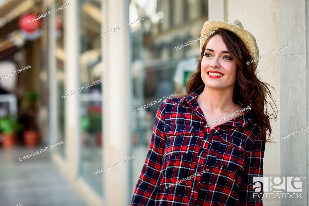 Stock Photo: Young woman with beautiful blue eyes wearing plaid shirt and sun hat. Girl smiling in urban background.