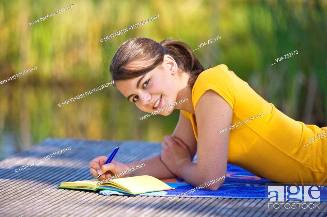 Stock Photo: Teenaged girl lying on a footbridge and writing in her diary, smiling at the camera.