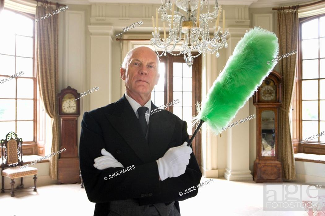 Stock Photo: Butler with duster, arms crossed, portrait.