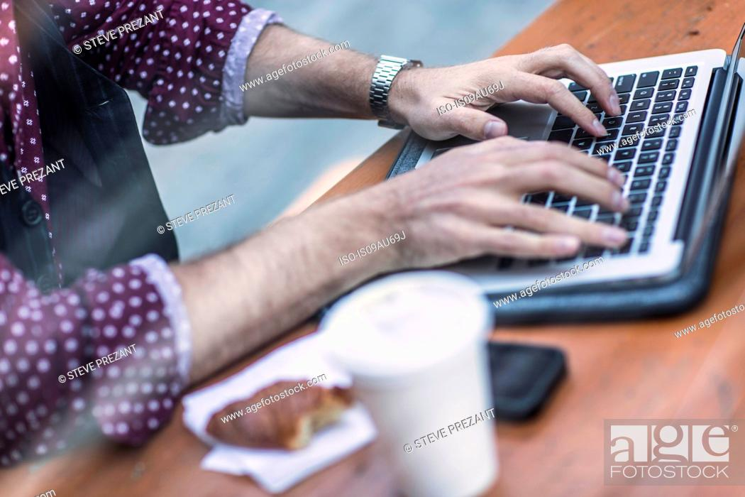 Imagen: Cropped view of young businessman typing on laptop keyboard at sidewalk cafe.