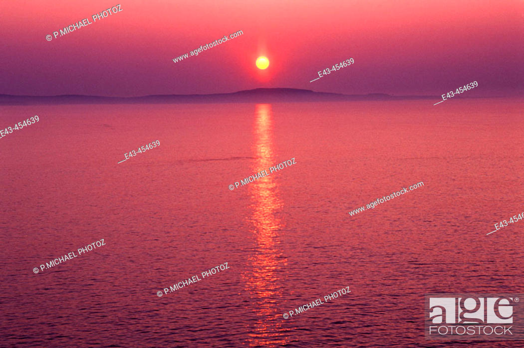 Stock Photo: Sun rising over a lake with mist - orange and red in colors.