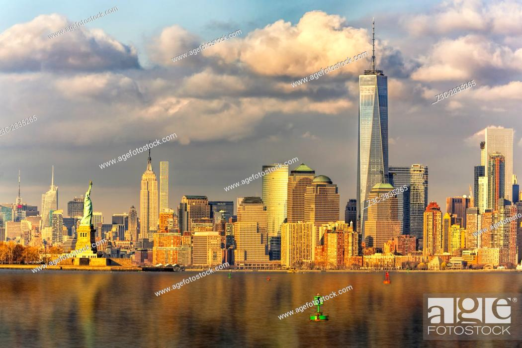 Stock Photo: New York City Icons II - The setting sun warms the midtown Manhattan skyline with the Empire State Building (ESB). Also seen is the Statue of Liberty in the New.