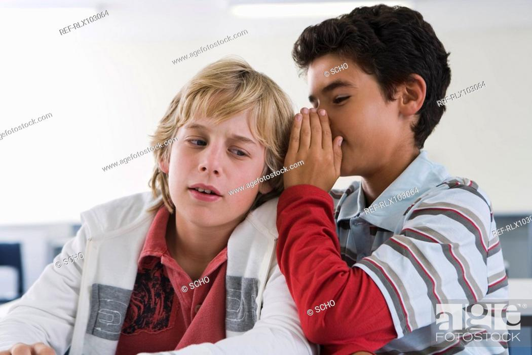 Stock Photo: Two boys 10-13 in classroom whispering.