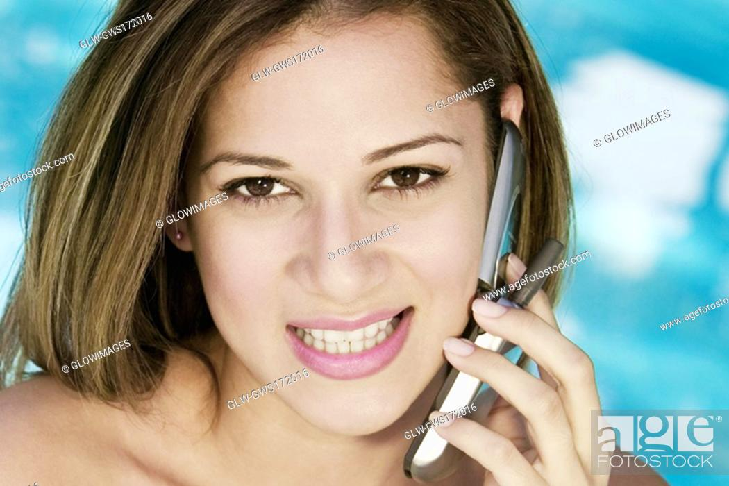 Stock Photo: Portrait of a young woman using a mobile phone and smiling.