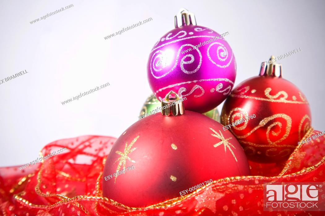 Stock Photo: Red bauble and red ribbon over a white background.