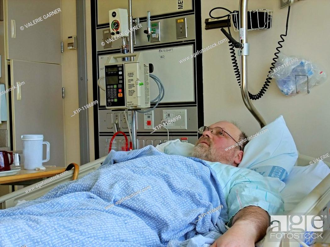 Stock Photo: This image is a middle aged bearded Caucasian man who's lying in a hospital bed in the hospital with a tray beside the bed and other medical objects.