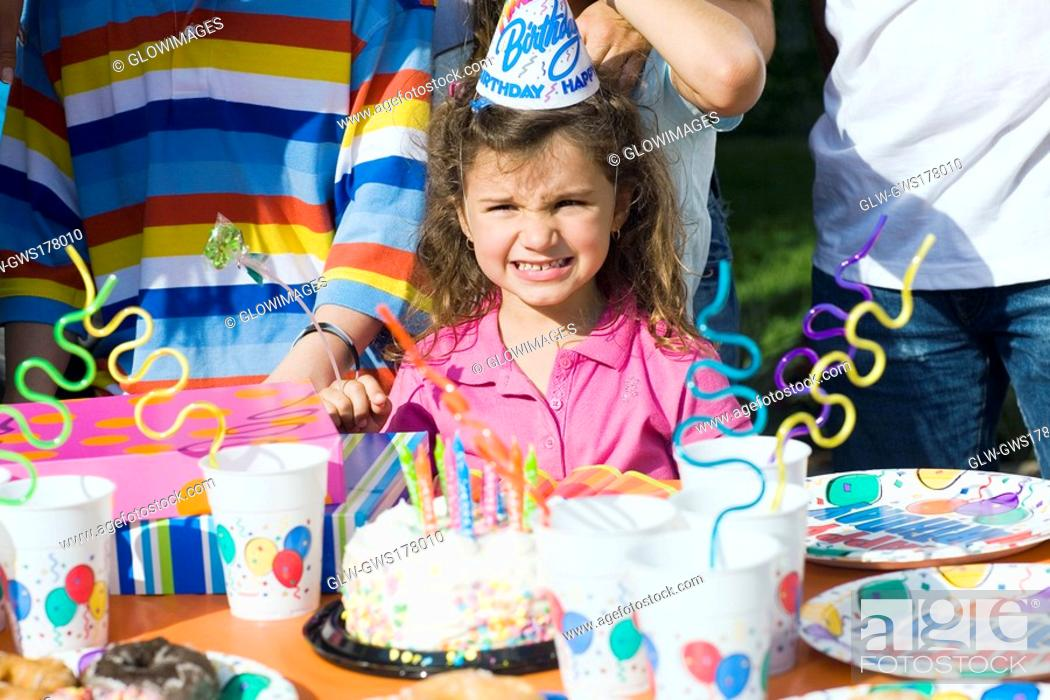 Stock Photo: Portrait of a girl standing in front of a birthday cake.