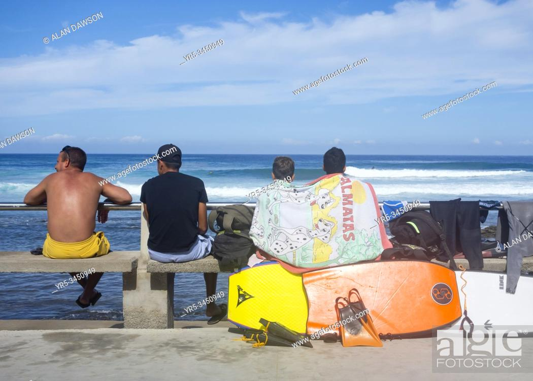 Stock Photo: Surfers and bodyboarders looking out to sea at El Fronton on Gran Canaria, Canary Islands, Spain.