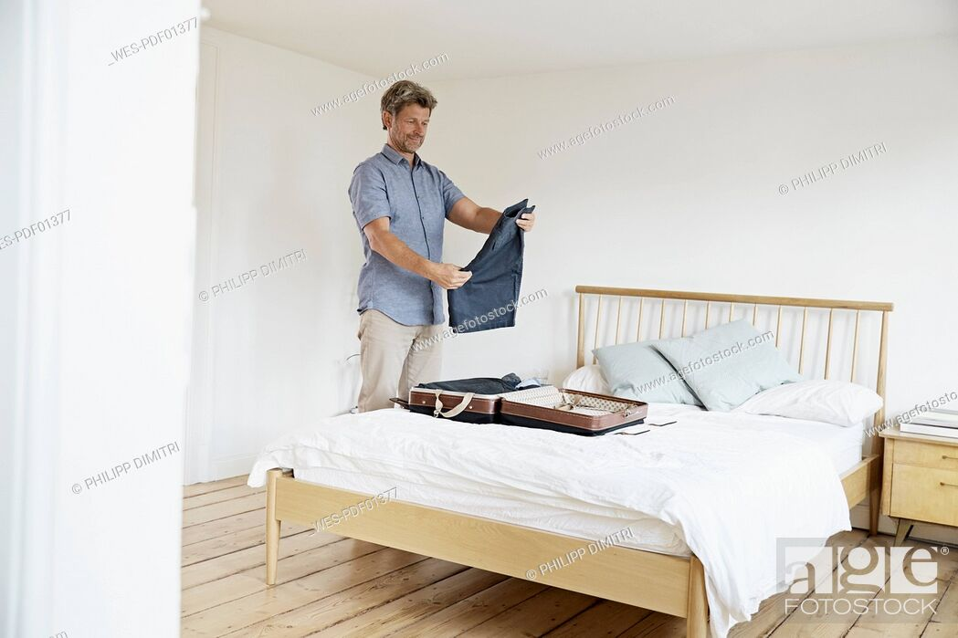 Stock Photo: Mature man packing suitcase in bedroom.