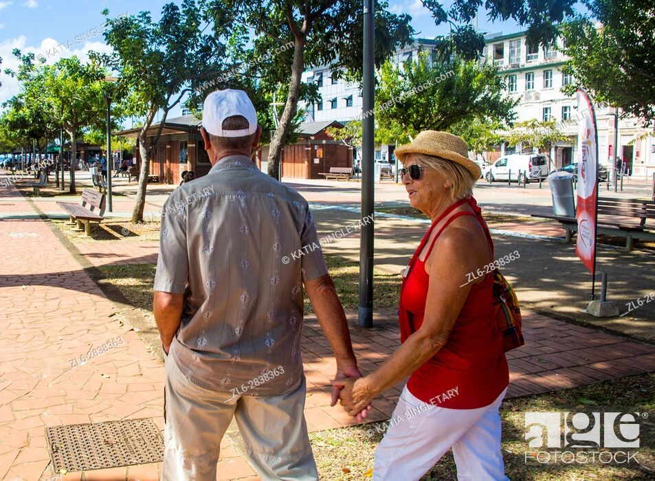 Stock Photo: Older mature retired caucasian couple holding hands in the streets of Fort de France on a vacation. He wears a baseball hat and she a straw hat.