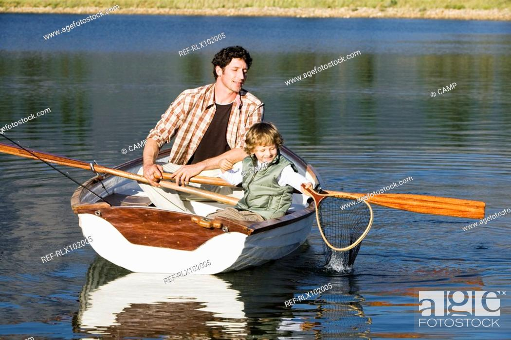 Stock Photo: Father and son 4-7 in rowing boat with fishing net, on lake.