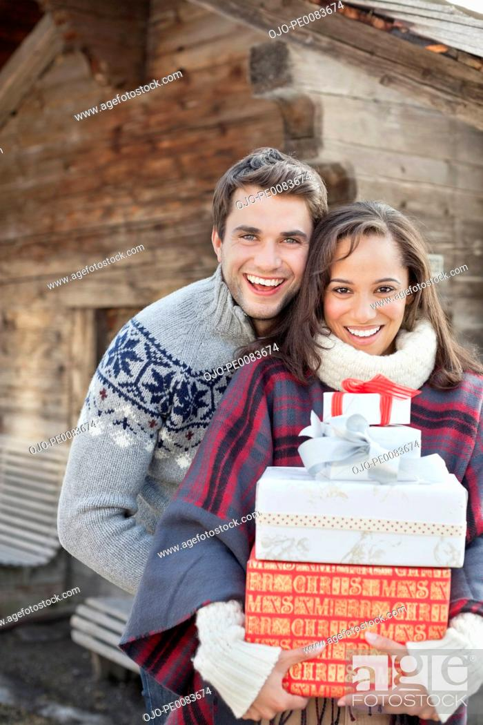 Stock Photo: Portrait of smiling couple holding Christmas gifts in front of cabin.