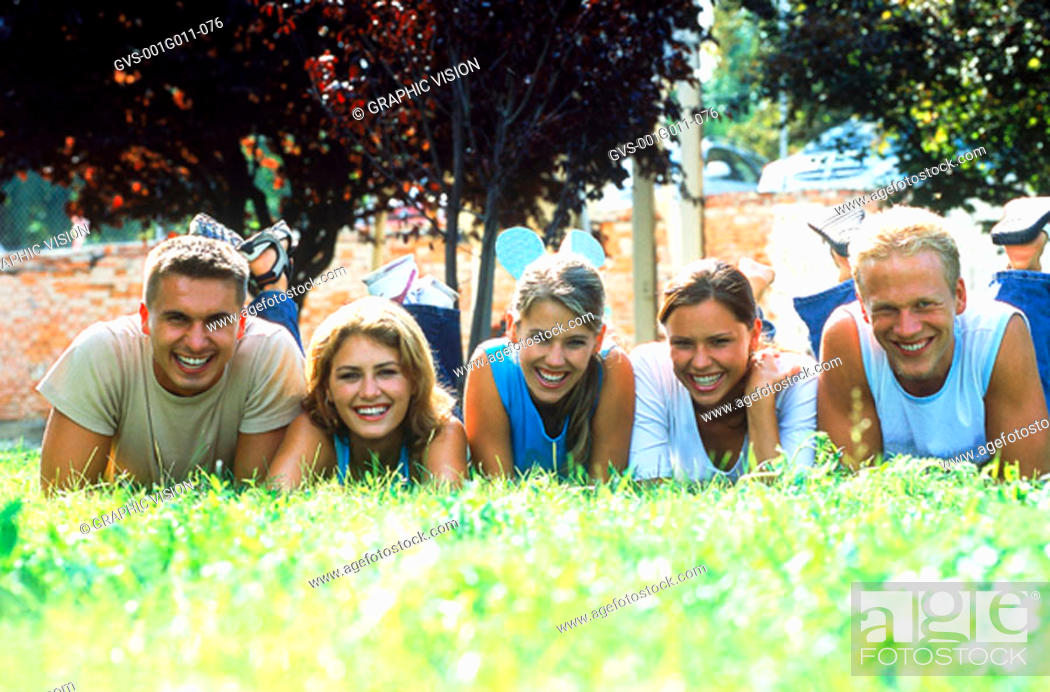 Stock Photo: Portrait of a group of young people lying in the grass.
