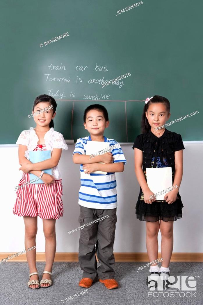 Stock Photo: Child, Three children standing in a row and holding book with smile.