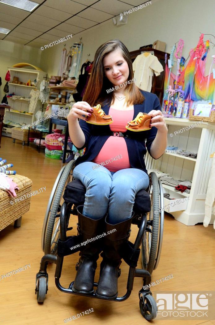 387477fab4850 Stock Photo - Pregnant paraplegic woman in wheelchair shopping in baby store