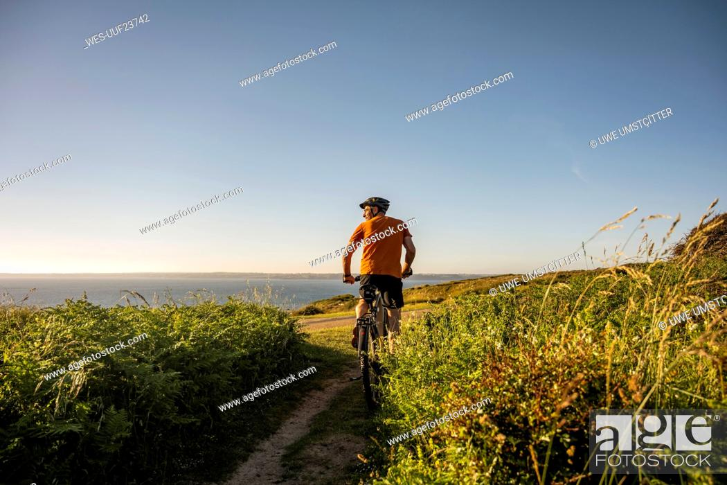 Stock Photo: Mature male athlete riding electric mountain bike amidst plants at sunset.