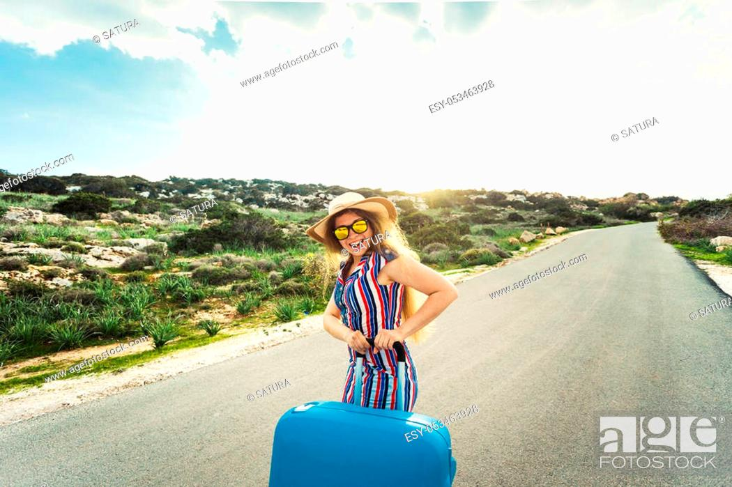 Stock Photo: Travel, holiday, summer and vacation concept - Young woman is standing and laughing on road with suitcases.