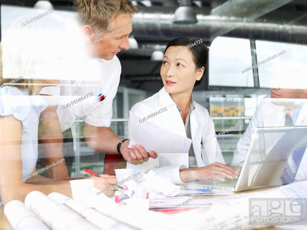 Stock Photo: Businesspeople working on laptop and blueprints.