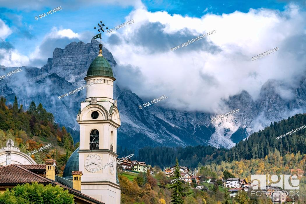 Stock Photo: The church tower of Santa Maria Nascente, the local church of Agordo, against the high rising mountains of the Dolomite mountains.