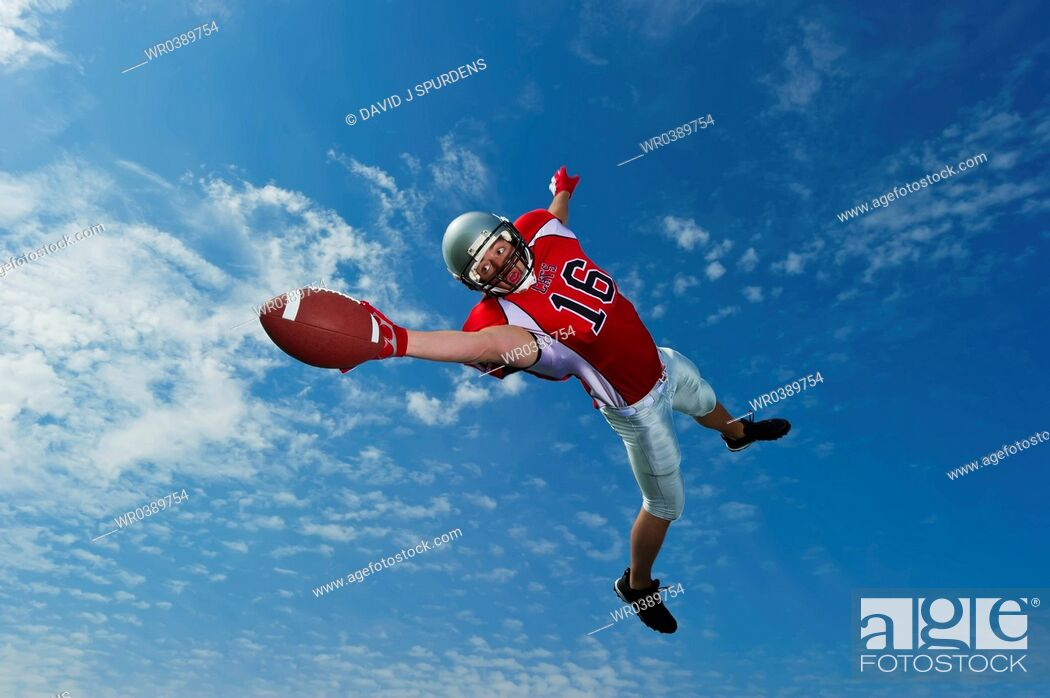 Stock Photo: American footballer in mid air stretches to make the catch.
