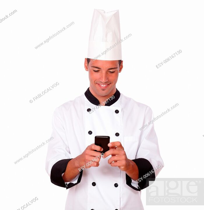 Stock Photo: Portrait of professional young chef on white uniform texting a message with his mobile while smiling and standing on isolated studio.