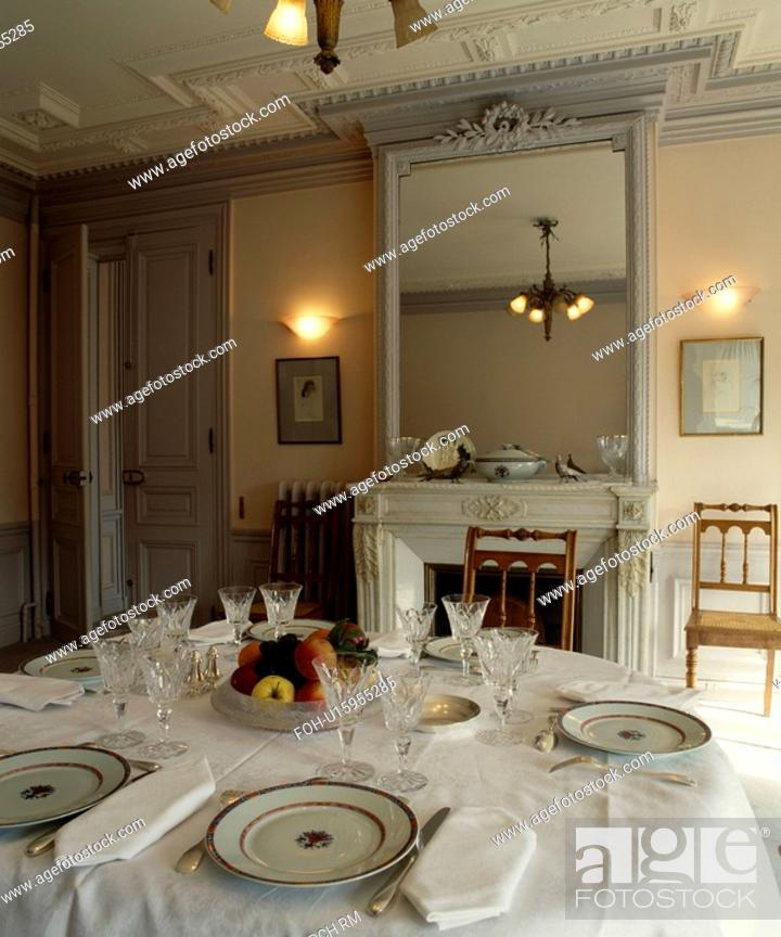 Stock Photo Wall Lights On Either Side Of Ornate Grey Mirror In Traditional Dining Room With Place Settings White Tablecloth