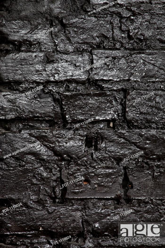 Stock Photo: A brick wall painted black, full frame.