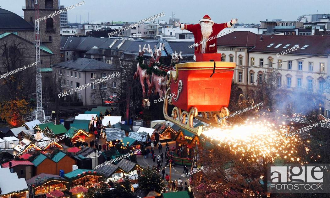 Stock Photo: The high-wire artist Falko Traber stands in a sled dressed as Father Christmas above the Christmas market in Karlsruhe, Germany, 05 December 2017.