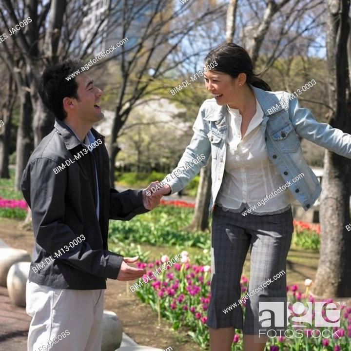 Stock Photo: Asian couple laughing and holding hands in urban park.