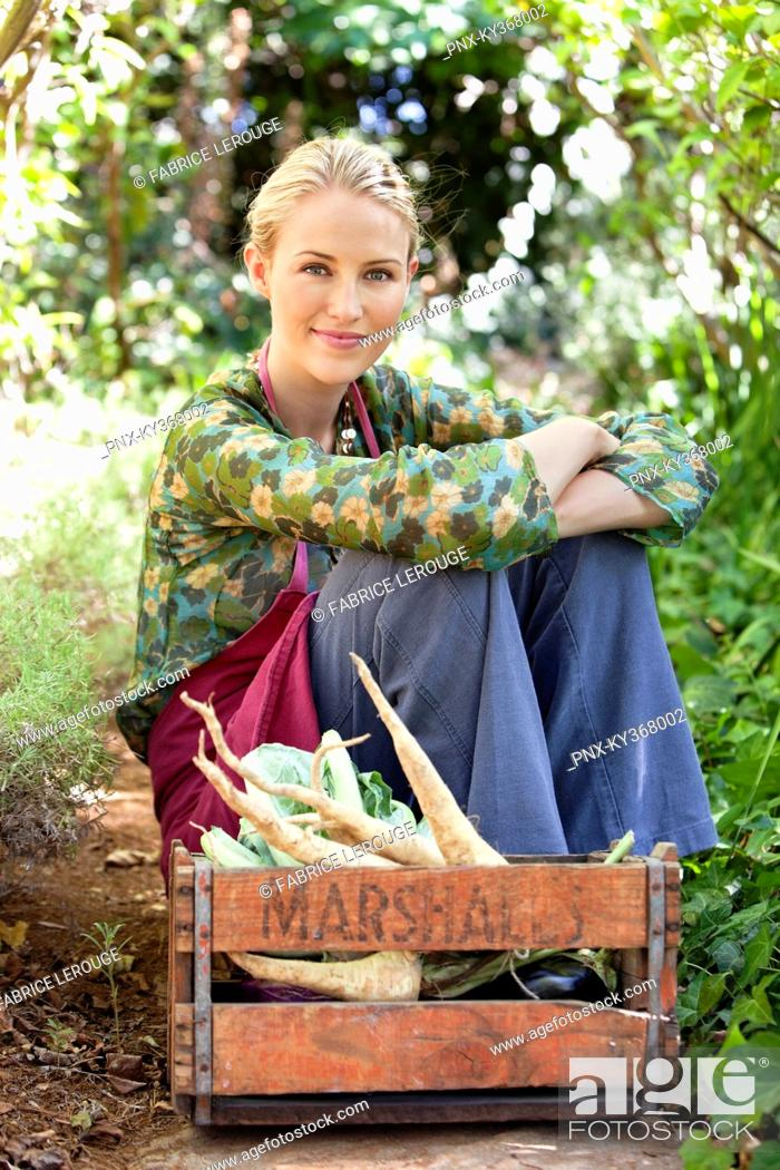 Stock Photo: Smiling woman sitting near a crate of vegetables.