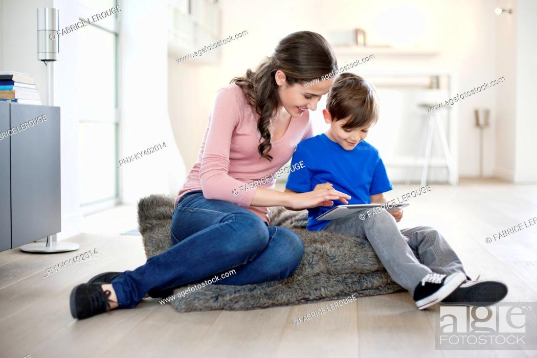 Stock Photo: Woman looking at her son using a digital tablet.