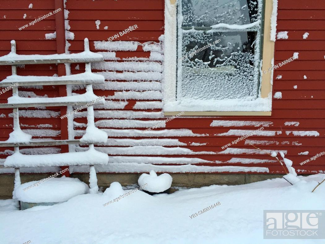 Stock Photo: Snow collecting on the side of a red house after a winter storm.