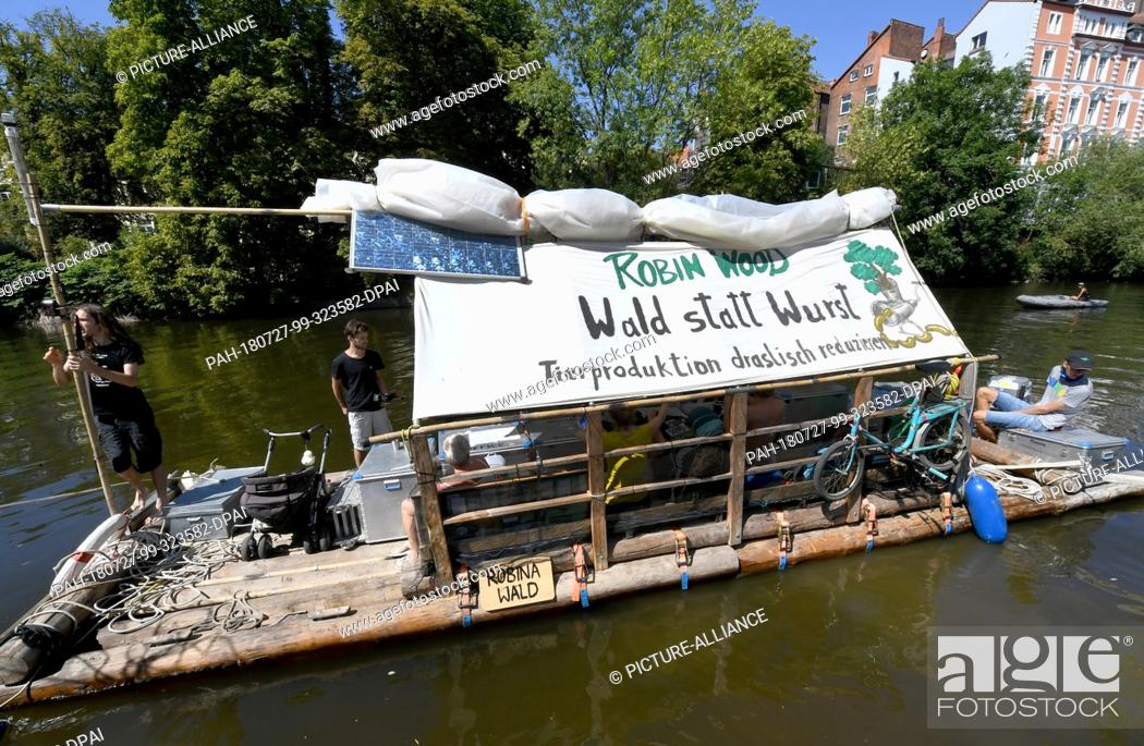 Stock Photo: 27 July 2018, Germany, Hanover: A raft of the environmental and nature conservation organisation Robin Wood floating on the Ihme River with tour participants.
