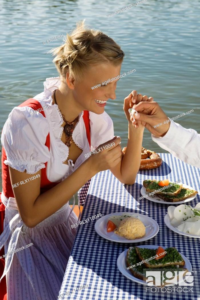 Stock Photo: Young woman in traditional Bavarian outfit, eating meal in beer garden, Munich.
