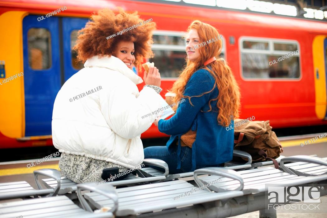 Stock Photo: Friends on bench on train station platform, London.